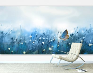 Mysterious soft blue misty morning in the meadow with flying butterfly