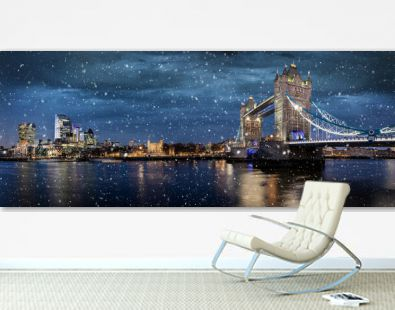 Panoramic view of the illuminated skyline of London, United Kingdom, during winter night time with falling snow over the Tower Bridge and City