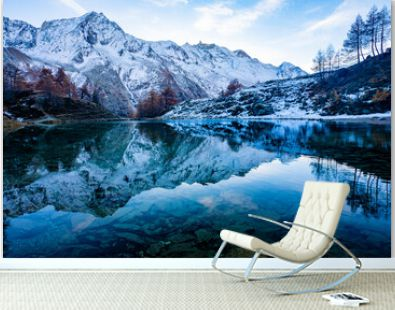 Reflections of snow capped mountains in a blue icy lake in the mountains