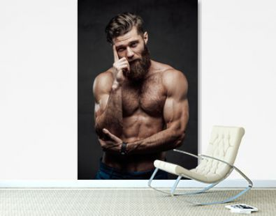 Bearded and shirtless guy with modern haircut and huge biceps posing with finger to his head in dark background.