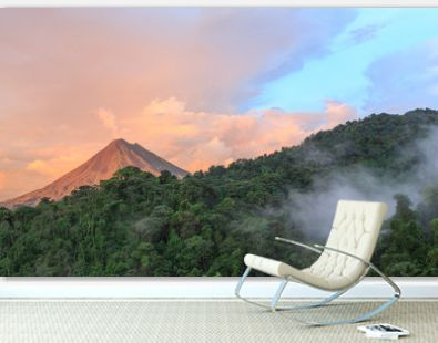 Sunset by Arenal Volcano in Costa Rica, cloud forest clouds rise from the jungle floor