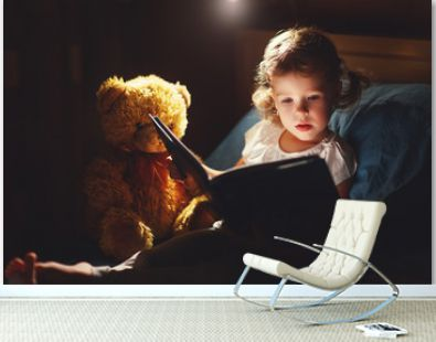 child girl reading book in bed