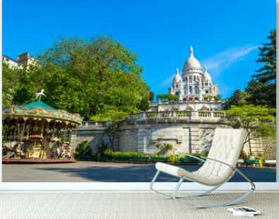 Sacre Coeur Basilica in Paris at day with blue bright sky and green grass and blooming trees.