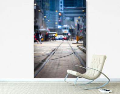 Hong Kong Street View / Streetcar tracks toward blurred urban traffic background with tram, car, unrecognizable people and city buildings at night (copy space)