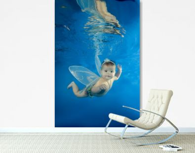 A little girl in a fairy costume swims underwater in the pool