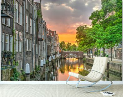 Fiery sunset reflecting in a canal lined with houses in the medieval town centre of Dordrecht, the Netherlands