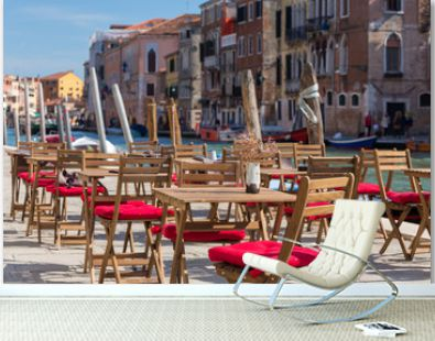 Street view of a cafe terrace with empty tables and chair in Venice, Italy.
