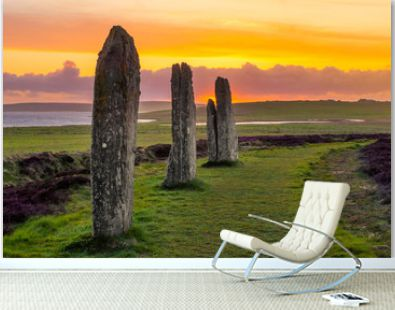Theree standing stones of the ancient and mysterious Ring of Brodgar underneath a dramatic sunset