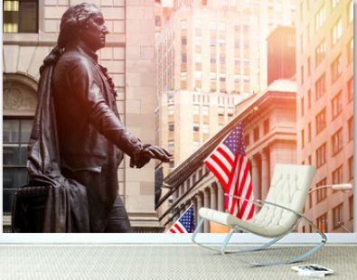 Wall Street in New York City at sunset with the statue of George Washington at the Federal Hall