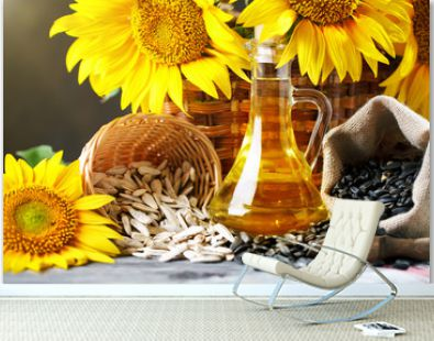 Closeup photo of sunflowers and sunflower oil with seeds on on a wooden table. Bio and organic concept of the product.
