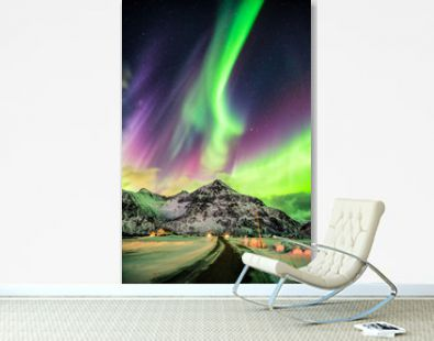 Aurora Borealis (Northern lights) explosion over mountains and rural road