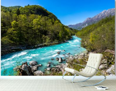 Famous river Soca near city of Kobarid. Beautiful emerald, green and blue wild river Soca, Julian alps, Slovenia. Blue sky, flowing alpine river, green trees and alpine peaks in background.