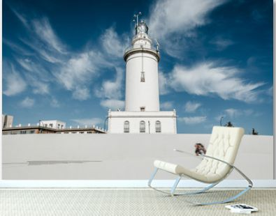 White lighthouse with blue sky background, and people walking in the street.