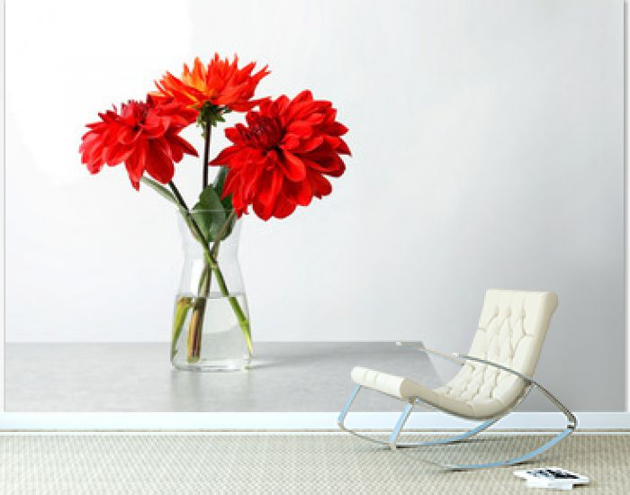 Vase with beautiful dahlia flowers on table against light background. Space for text