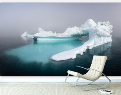 Panorama of a massive iceberg with a smooth underwater shelf on a foggy day. Disko bay, Greenland.