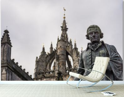 Edinburgh, Scotland, UK - June 14, 2012: Adam Smith bronze statue on market square in front of brown stone Saint Gilles Cathedral crown tower under gray silver sky.