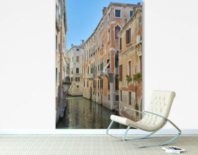 Venice canal with ancient buildings and houses facades in a sunny day in Italy