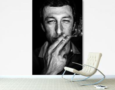 Happy man smokes a cigarette, a creative portrait of a real man, a black and white image