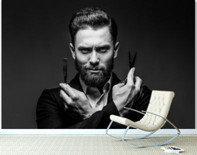 Portrait of bearded hipster male barber holds sharp scissors and a blade isolated on gray backgrund