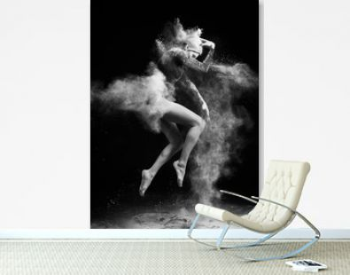 Beautiful slim girl wearing a gymnastic bodysuit covered with clouds of the flying white powder jumps dancing on a dark. Artistic conceptual and advertising black and white photo.