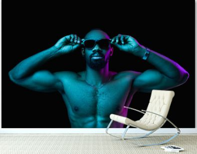 Close up portrait of a young naked happy smiling african man in sunglasses at studio. High Fashion male model in colorful bright lights posing on black background. Art design concept
