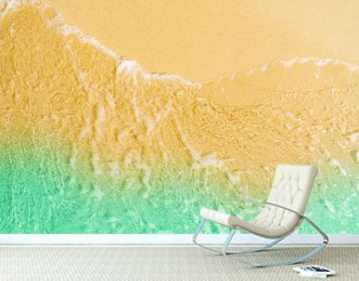 Top view of golden sand beach by the sea with emerald green sea water. Summer vacation on tropical paradise beach concept. Ripple of water splash on sandy beach. Summer vibes.