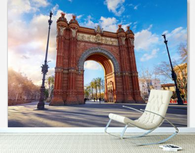 Sunrise at Triumphal Arch in Barcelona, Catalonia, Spain. Arc de Triomf at boulevard street. Alley with tropical palm trees. Early morning landscape with shadows and blue sky with clouds. Famous.