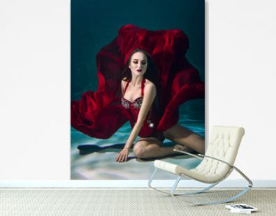 Girl portrait posing underwater in red fashion dress in swimming pool alone in the deep