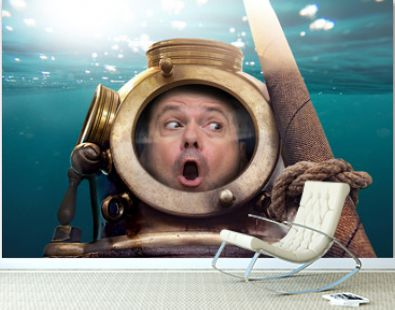 Portrait of man in old diving suit and helmet under water. Funny diver in retro equipment in amazement looks around.