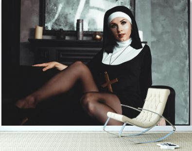 Sexy nun prays indoor . Beautiful young holy sister. Young beautiful nun with a cross in a robe in a black interior.