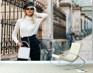 Outdoor street fashion portrait of elegant lady wearing stylish autumn outfit: black leather beret, sunglasses, white turtleneck, checkered high waist trousers, small bag, posing in city. Copy space