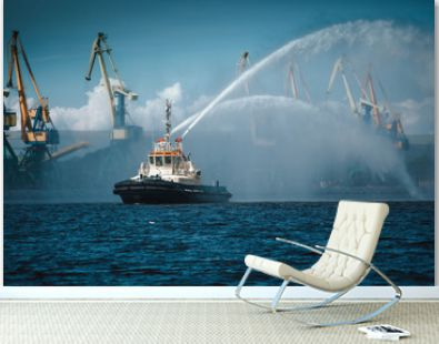 A firefighter floating modern tug boat sprays jets of water