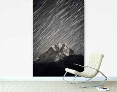 Stars falling above Ama Dablam mountain peak lit up by a bright moonlight. Stars trails above Himalayan mountain range.