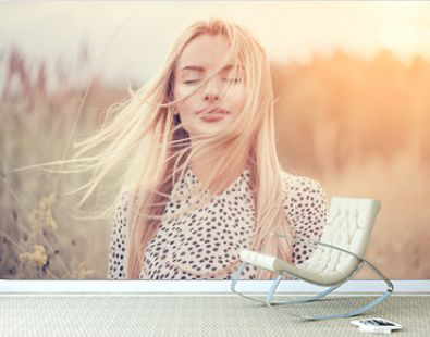 Close Up Portrait of beauty girl with fluttering white hair enjoying nature outdoors, on a field. Flying blonde hair on the wind. Breeze playing with girl's hair. Beautiful young woman face closeup.