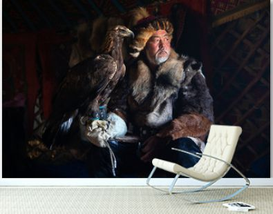 Portrait of an old kazakh eagle hunter with his majestic golden eagle indoors in dark traditional kazakh ger. Ulgii, Western Mongolia.