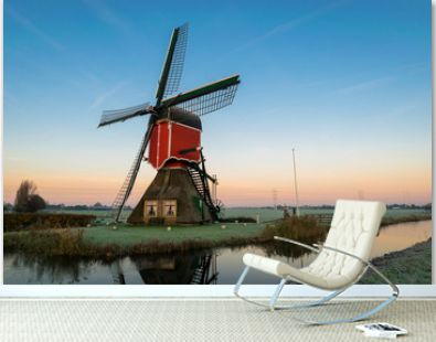 Stunning landscape image of a traditional dutch windmill at sunrise on a cold morning in autumn