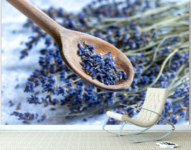 Spoon with dried lavender flowers on blurry background