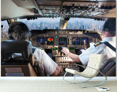 The cockpit of a modern passenger aircraft in flight. Pilots at work. A view from the cockpit to the skyscrapers of the business center of a huge city.