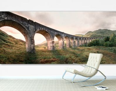 Glenfinnan Railway Viaduct. Harry Potter famous Glenfinnan viaduct, Scotland in cloudy weather and sunrise in the background.