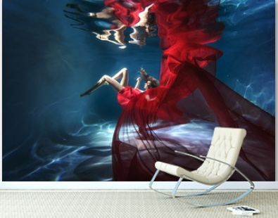 Underwater scene. A woman, a fashion model in the water in a beautiful dress swims like a fish.