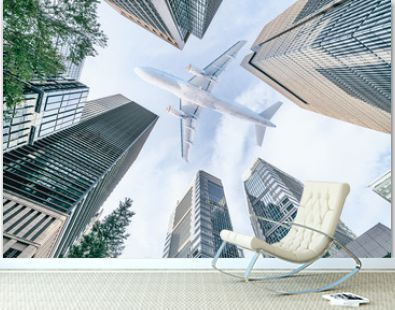 Aircraft flying above glass office buildings in the sky over city buildings in financial district of Tokyo city, Japan