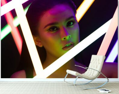 Face Close up of High Fashion Trend Cosmetic make up with NEON tube light, effect on skin of young Asian Woman in low exposure, express feeling by color of LED line, copy space black backgrounds