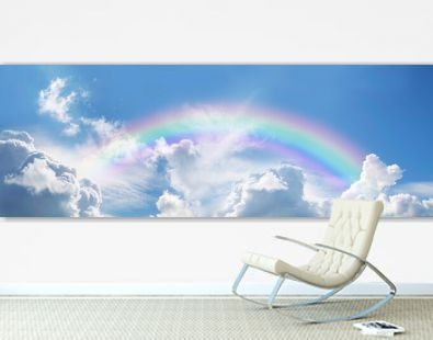 Stunning blue sky panoramic rainbow - big fluffy clouds with a giant arcing rainbow against a beautiful summer time blue sky with copy space for messages