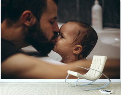 selective focus, noise effect: bearded father is washing and bathing the baby in the bathroom, child girl have fun, she is happy and smiling, likes to enjoy water