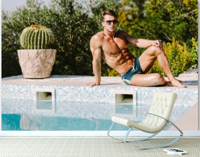 Sexy muscular man in swim trunks relax and posing near swimming pool outdoors. Muscular sports male model wearing sunglasses relax and sunbathe outdoors