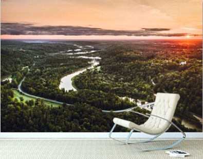 Picturesque valley of Sigulda city in sunrise colors. Panoramic view over pine forest surrounding river Gauja.