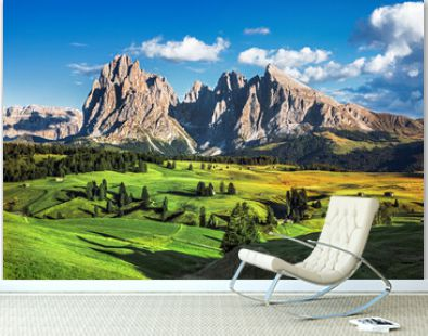 Famous Alpe di Siusi - Seiser Alm with Sassolungo - Langkofel mountain group in background at sunset. Wooden chalets in Dolomites, Trentino Alto Adige region, South Tyrol, Italy