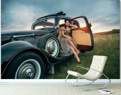 Young beautiful sexy woman in pin-up style clothes sits posing in black retro car. Polka dot white dress, vintage hairstyle, red high heels. Background road nature summer. Girl fashion model driver