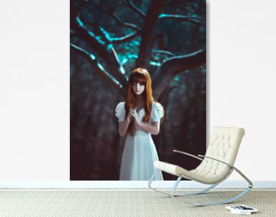 Young beautiful red-haired lady girl, stands in mystical dark deep dense forest hands folded in prayer. Night background, wood tree moon light. White long vintage dress. Scared medieval princess girl.