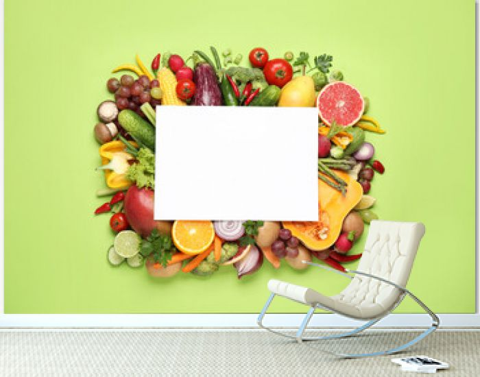 Fresh organic fruits, vegetables and blank card on green background, flat lay. Space for text